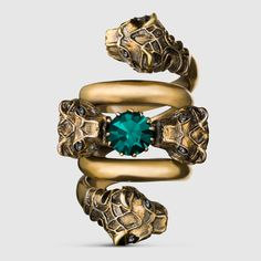 Gucci double wrap tiger head ring in metal with an aged gold finish. The center stone is a green Swarovski crystal and the tiger eyes are black Swarovski crystals.