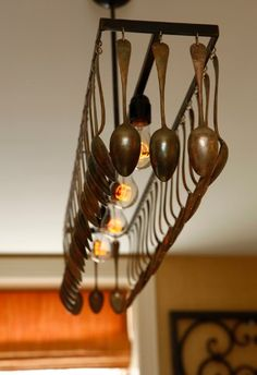 repurposing a pot & pan hanger with soup spoons on the pan hooks and hanging it over a track light fixture!
