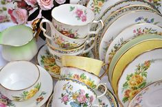 A colourful mixed vintage china tea set with a three tier cake stand. Primrose yellow, lime green and pretty florals. cakestandheaven.com