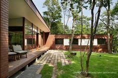 レンガの外壁でもモダンなデザインに。森のなかにすっと馴染むような外観と落ち着いた室内空間をご提案しています。[外観 エクステリア 芝生 庭 image]