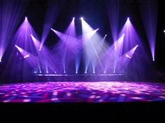 The lights are pointing in all different directions which creates the feeling that the beams of light are actually taking up space. The colors also create a calm atmosphere for me because I find purple to be a relaxing color. The designs on the stage however, contradict that relaxing feeling because they remind me of some sort of germ or caterpillar.