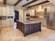 LOVE this kitchen - like how the countertops pick up the colors of the cabinetry, island, and faux wood beams.