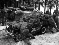 Battle of the Bulge. American GI's pushing a Jeep through the snow.