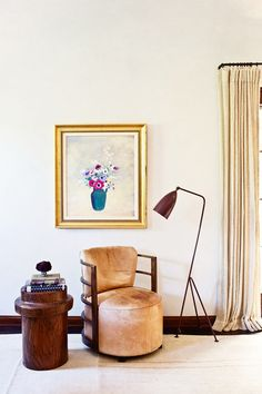 A reading nook in an eclectic bedroom with small antique artwork and floor lamp