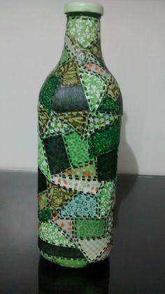 Garrafa de suco de uva reciclada, decorada com retalhos de tecido, com cor predominante em verde