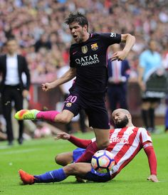 Barcelona's midfielder Sergi Roberto (top) is tackled by Sporting Gijon's defender Alberto Lora during the Spanish league football match Real Sporting de Gijon vs FC Barcelona at El Molinon stadium in Gijon on September 24, 2016. / AFP / ANDER GILLENEA
