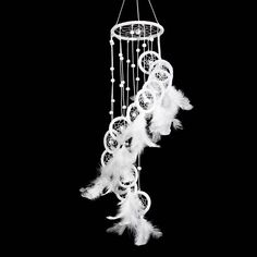 The feathers in this mobile dreamcatchers are in white and hang from long white ropes, pearl white beads are also added to the hanging strings. More than 10 small dreamcatchers hang from the top hoop. The hoops of these small dreamers have been straight crochet around with white strings and decorated either with feathers and beads.
