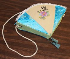 A fan shape gives this Asian-inspired purse a very unique look, and decorative trim and tassels make it seem fancy with a flourish!    With fabrics and embroidery designs of your choosing, you can make this fabulous purse uniquely personal, as well.    Read on for project instructions to create a beautiful and stylish purse!