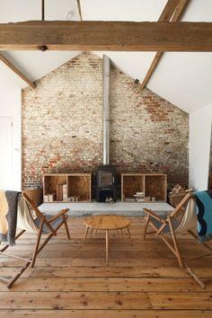 rustykalny salon, ale w nowoczesnym wydaniu - w tle ściana z czerwonej cegły,proste, drewniane meble oraz żeliwny, czarny kominek o prostej formie