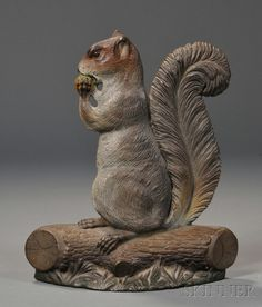 Painted Cast Iron Squirrel Doorstop, attributed to Bradley & Hubbard, Connecticut, late 19th/early 20th century, the figure seated on a log and eating a nut, fine original polychrome-painted surface, with two rubber bumpers applied to the back of the base, ht. 12, wd. 10 1/4 in.   Sold for $ 4,029