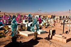 The San Pedro de Atacama cemetery and paper flowers on the graves for the Day of the Dead. One of the most beautiful cemeteries in South America, surrounded by Andes volcanos.