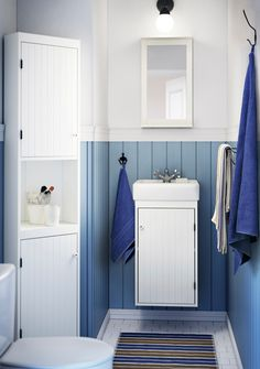 A small bathroom with a white wash-basin cabinet, a corner cabinet and a mirror.