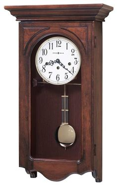 """This wall clock offers a flat top pediment is accented with olive ash burl corner overlays. A hinged door completes the appealing design. An off-white dial features black Arabic numerals, black serpentine hour and minute hands. A brass finished pendulum and bezel provide the perfect accents to the warm wood case. Finished in Windsor Cherry on select hardwoods and veneers. German made Key-wound, quarter hour Westminster chime movement with hour count. Size: H. 24-1/4"""" W. 13"""" D. 6-1/2"""""""
