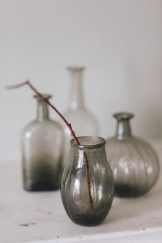 These lovely recycled glass bottles come in a variety of shapes. They look wonderful grouped together and are beautiful empty or can be used as vases. Sold as a set of 4. Colour: Smoke. Size: Approximately 17.5 x 12cm £29.95