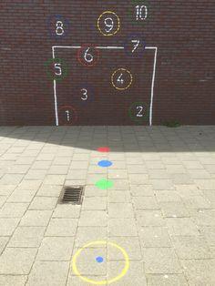 Schoolplein voetbaldoel en tennisbalspel. Start met je voeten op de rode stip. Gooi de bal tegen nr. 1 en vang de bal weer op vervolgens 2 tm 10 op dezelfde manier. Ben je bv. bij 3 en vang je de bal niet dan is de volgende speler aan de beurt. Na zijn beurt begin je weer opnieuw bij 3 en vervolgens 4 tm 10. Is dat gelukt dan ga je naar de blauwe stip 1 tm10 en groene stip 1 tm 10. Winnaar is de eerste die groene stip tm 10 heeft behaald!