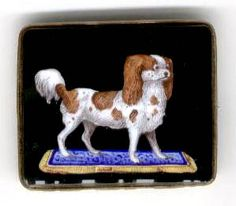 Brooch of an enamel painting of a King Charles spaniel standing on a colorful blue rug, mounted in 14k, circa 1860.