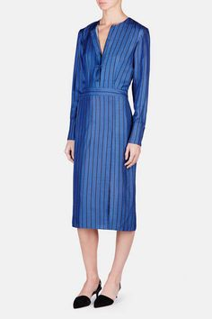 The spring 2016 collection from Protagonist is an exploration of fluidity and ease. Pieces such as this polished shirtdress balance serene femininity with menswear-inspired tailoring and finishes. Made in New York of washed silk twill, the collarless style has a placket of five covered buttons that are reprised along the extended, four-button cuffs. A precisely placed pattern of vertical lines visually elongates the body, while a contrasting panel of horizontal stripes accents the waist.