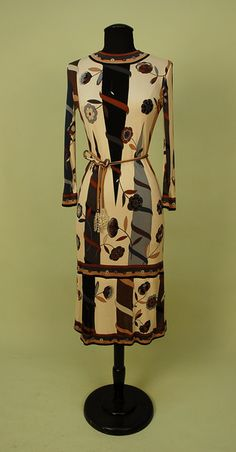 """PUCCI PRINTED SILK JERSEY KNIT DAY DRESS, c. 1960. Long sleeve, over the knee length with signature """"Emilio"""" print having vining flowers on pointed columns in black, brown, slate and tan on cream ground with stripe and circle bands, self belt with crystal bead tassels. Label """"Emilio Pucci Florence-Italy"""". Bust 36, waist 28, length 44. Few tiny spots on bodice front, otherwise excellent. $431.25."""