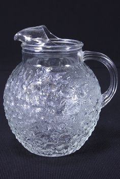 This listing is for a vintage clear glass ball-style pitcher with 12 cup capacity, made by Anchor Hocking Glass Company in their Lido Milano pattern. It has a large ice lip, a ridged and rounded handl