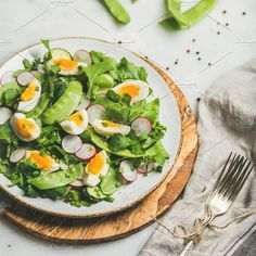 #Healthy spring green salad  Healthy spring green salad with radish boiled egg arugula green pea and mint in white plate on olive tree wood board over grey background selective focus square crop