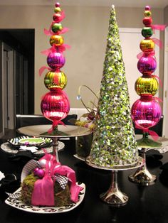 Colorful and Cheery    Spice up your tabletop with a centerpiece of glittering trees and stacked ornament topiaries. RMSer ms mags creates interest by placing the items on cake plates of varying heights.