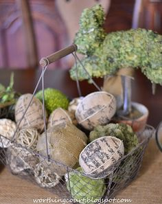 An Easter centerpiece with an aged wire basket filled with burlap eggs and a variety of decorative orbs