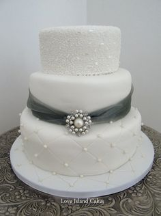 PEARLS AND SPARKLE WEDDING CAKE  Three tier cake with hand piped lace with added sparkle and pearl cushion detailing, brooch supplied by the Bride