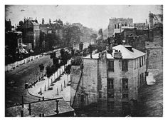 Boulevard du Temple, Paris, Spring 1838, by Daguerre. The image shows a busy street, but because the exposure time was at least ten minutes the moving traffic cannot be seen. However, two men at lower left, one apparently having his boots polished and the other the bootblack, remained motionless enough to be distinctly visible. The image is reversed (as were most Daguerreotypes) as is evidenced by the signage on a building in upper left.