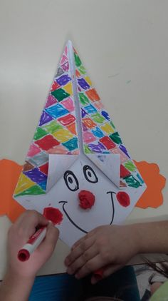 Με χαρτοδιπλωτική σχηματίσαμε τους κλόουν και με τον χάρακα χωρίσαμε το καπέλο σε ρόμβους.Στην συνέχεια τα παιδιά έβαψαν κάθε ρόμβο με άλλο χρώμα,ζωγραφίσανε τα μάτια,το στόμα,τα μάγουλα και τέλος …