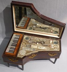 Antique Palais Royal musical Grand Piano sewing box. The carcase of high quality flame mahogany with gilt bronze mounts and ebonised legs. Lift the lid and the sewing compartment is revealed with Palais Royal mother of pearl sewing items.  If you depress a set of keys on the left hand side it sets off the music box fitted in the compartment below the sewing tools. Circa 1830.