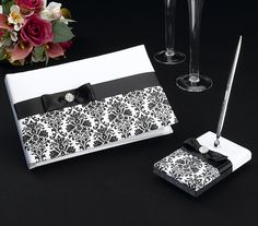"""This Black Damask Guest Book set includes a 10"""" x 6.5"""" guest book and a pen set with 3.25"""" x 5.25"""" base.  Both are covered in beautiful white satin and decorated with black satin ribbon, a black satin bow and a rhinestone ornament.  Below the ribbon is an elegant silkscreened damask pattern.The book holds 30 pages for a total of 580 signatures.  The pen is silver with black ink.Added January 9, 2012 et"""