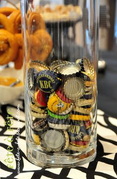 beer bottle tops in glass container --- bar decor + wastebasket https://antiherobrewing.wordpress.com/2015/01/05/sam-adams-and-why-we-need-to-stop-listening-to-hipsters/