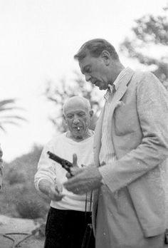 Gary Cooper giving Pablo Picasso instructions on handling a pistol.