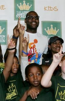 """NBA star and Akron native LeBron James and his mother Gloria James, right, pose with children participating in the LeBron James Family Foundation's Wheels for Education """"Time to Promise"""" School Year event at Canal Park during an Akron Aeros game Sunday, Aug. 19, 2012 in Akron, Ohio."""
