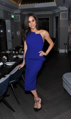 Embracing the cold shoulder trend in this electric blue dress./Meghan Markle