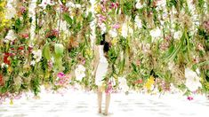 Floating Flowers installation by TeamLab at Miraikan in Tokyo - Room full of suspended flowers that are digitally-controlled, and rise into the air as someone walks towards them, creating an 'air bubble' within the dense vegetation. Multiple viewers can walk through the floating garden at once, causing a lot of activity as the flowers move away from them and surround them