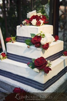 White wedding cake with red and white rose accents, and blue grey ribbon trim