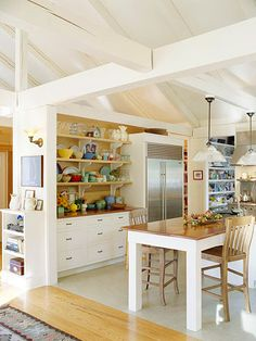Cohesive Look  White beams, ceiling, and cabinetry create a unified look that is light and bright. The support beams visually lower the ceiling for a cozy feel. They also offer a convenient location for installing pendant lighting over the island.