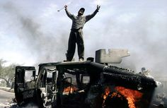 An Iraqi man celebrates atop of a burning U.S. Army Humvee in the northern part of Baghdad, Iraq. This photograph, taken by Muhammed Muheisen, was one in a portfolio of twenty taken by eleven different photographers throughout 2004 that won the Pulitzer Prize the following year.
