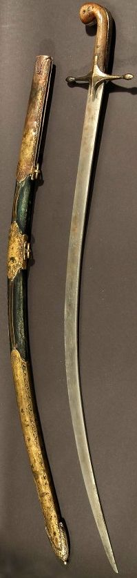 Ottoman shamsir, 19th century, curved 78.7 cm (31 in.) single edged blade. Brass crossguard of characteristic form. Horn gripscales, the silver sidestraps chased with florals. Green leather-covered scabbard, the brass mounts chased with floral borders.