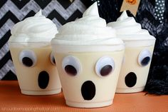 Create these fun #ghost pudding cups by gluing some googly eyes onto a plastic cup, drawing a black circle for a mouth, and filling them with your favorite vanilla pudding. Perfect for Halloween parties! #DIY #Halloween