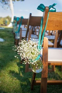 Mason Jars Hanging from Chairs With A Turquoise Bow. Pefect For a Beach Theme Wedding.