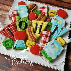 Backyard barbeque themed decorated sugar cookies for a kid birthday party. Gingham pennant banner, hot dog cookies, grill cookies, picnic cookies.