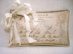 Sweet sachet created with fabric printed with a vintage French postcard image, accented by a crinkled, seam binding bow and an antique button, and filled with lavender buds