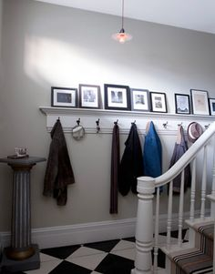 Black-and-White Foyer.  I love the picture rail / coat and hat rack in the front hallway, as well as the dainty light hanging down and the column-entry table