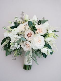 BRIDE BOUQUET: A lush naturally shaped bouquet of ivory playa blanca roses, white lisianthus, blush quicksand roses, and white ranunculus with the greenery of nagi, silver dollar eucalyptus, and seeded eucalyptus wrapped in an ivory ribbon with the stems exposed