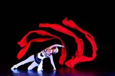 Dancer with red ribbon triton. Black light performance Crystal UV Light Show.