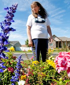 Sandy Krambule walks outside her Nibley, Utah, home where she has planted hundreds of various perennials and annuals. Krambule shares her love of gardening with others. (Photo by John Zsiray)