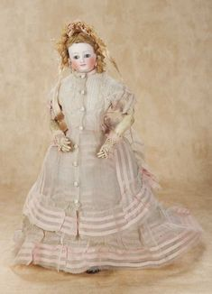 French Bisque Poupee by Doleac wearing a two-piece summer gown of fine sheer muslin with interwoven rose ribbon bands,matching bonnet,undergarments,leather slippers,rose fingerless woven gloves. Circa 1870.