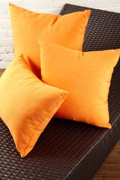 Brown-black wicker furniture with orange accent pillows. Guest room